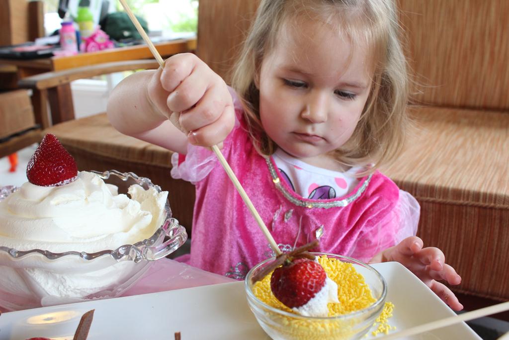 toddler girl dips strawberry wand sprinkles