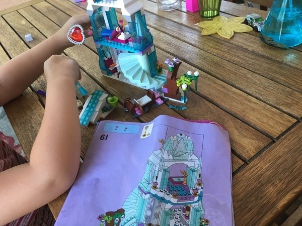 child hands building frozen lego set
