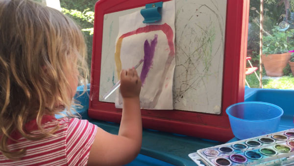 little girl painting at child's art desk