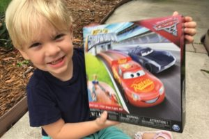 Boy Smiling with Cars 3 Pison Cup Showdown game